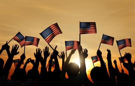 34537582 - group of people waving armenian flags in back lit