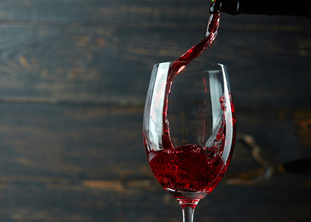 47409628 - pouring red wine into the glass against dark wooden background