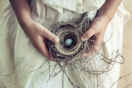 28851668 - vintage toned closeup of girl holding wild bird nest and blue egg